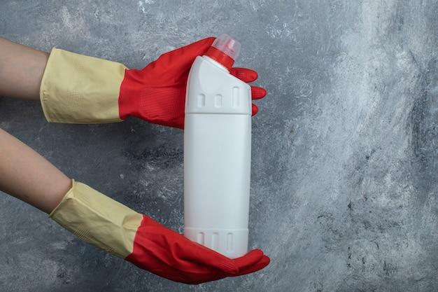 Manos en guantes protectores sosteniendo productos de limpieza.