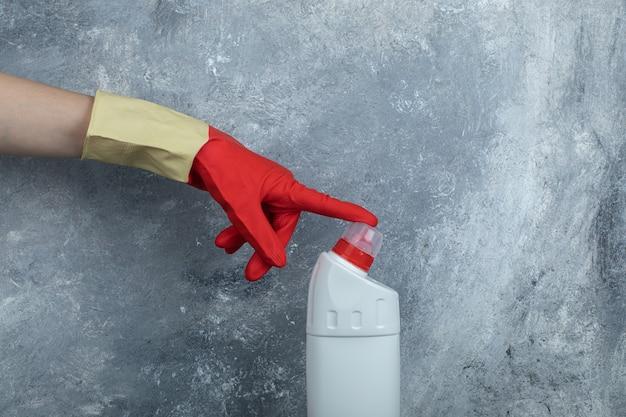Manos en guantes protectores tocando la punta del producto de limpieza.