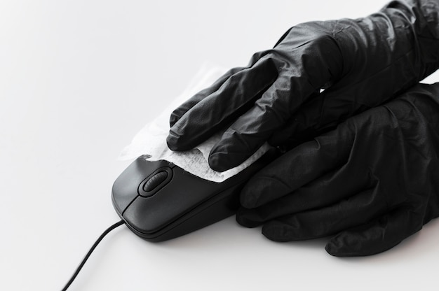 Manos con guantes quirúrgicos desinfectando el ratón