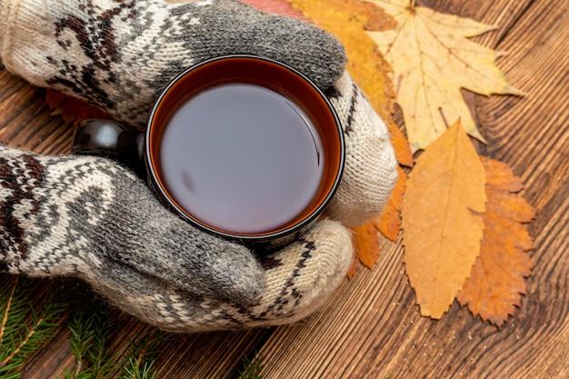 Manos en guantes sosteniendo una taza de té