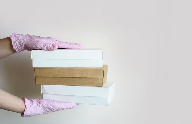 Las manos en guantes sostienen cajas de alimentos ecológicos para la entrega sobre un fondo claro. lugar para el texto