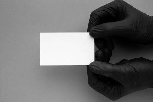 Manos en guantes con tarjeta de visita
