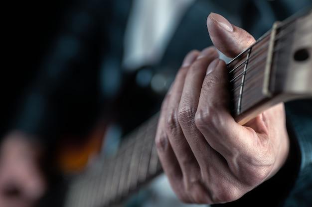 Manos de guitarrista y cuerdas de guitarra de cerca