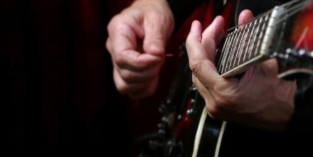 Manos de guitarrista y guitarra en una mesa negra de cerca. tocando la guitarra eléctrica. copie los espacios.