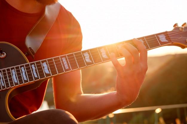 Manos del guitarrista tocando acordes de guitarra eléctrica al aire libre, tarde, puesta de sol