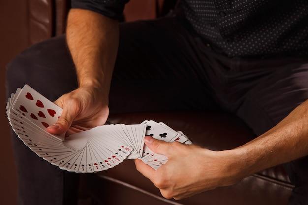Manos hábiles de mago. retrato de hombre joven con cartas de juego. chico guapo muestra trucos con tarjeta