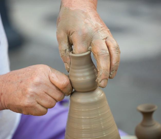 Manos haciendo cerámica en una rueda