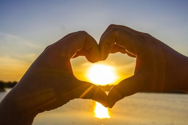 Manos haciendo la forma de un corazón con el sol en el medio.