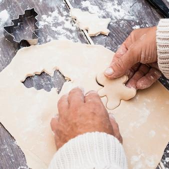 Manos haciendo hombre en forma de galleta de pastelería