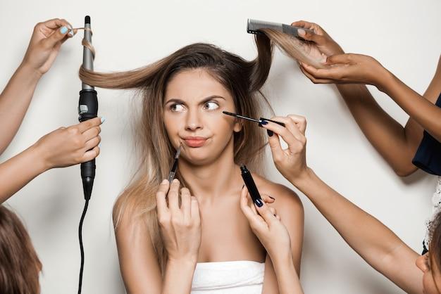 Manos haciendo maquillaje y peinado de joven bella mujer