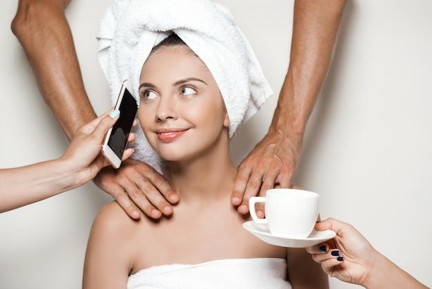 Manos haciendo masaje, dando teléfono y café a hermosa mujer