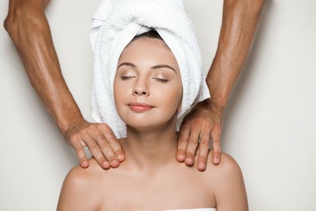 Manos haciendo masaje joven hermosa mujer en toalla