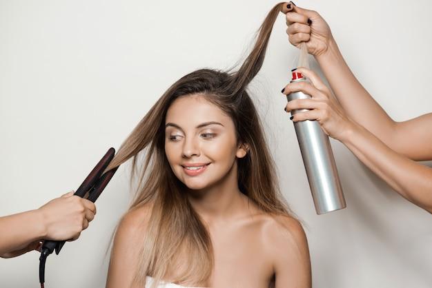 Manos haciendo peinado a joven bella mujer