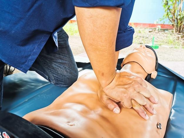 Manos haciendo una rcp bombeando el pecho al paciente ficticio