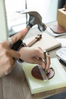 Manos haciendo trabajo de cuero, pin de sujeción de mano y martillo