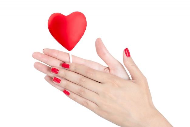 Manos hermosas de la mujer con el clavo rojo que sostiene la piruleta roja del corazón aislada en el fondo blanco