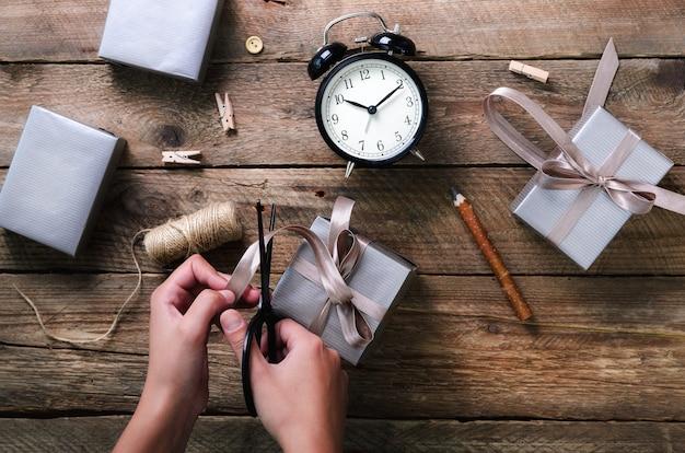 Manos hermosas de la mujer que sostienen la caja de regalo en de madera. despertador negro, pluma, tijeras.
