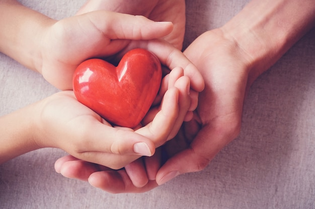 Manos holiding corazón rojo, concepto de familia de atención médica