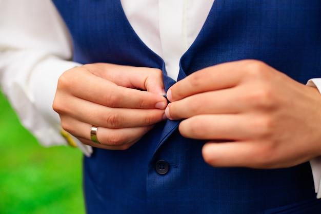 Las manos del hombre abrochan el botón del chaleco azul