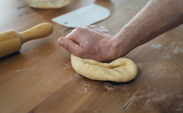 Las manos del hombre amasar pan en mesa de madera con rodillo de madera. concepto de panadería.