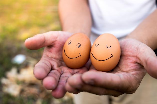 Las manos de un hombre para atrapar los huevos.