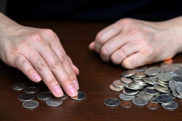 Las manos de un hombre clasificando monedas apiladas.