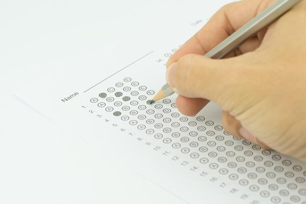 Manos del hombre completando un formulario de prueba estandarizado