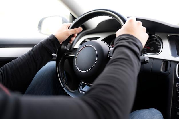 Manos del hombre conduciendo el volante