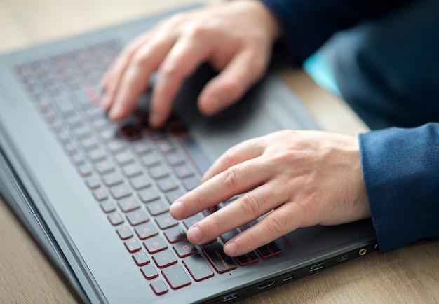 Manos del hombre escribiendo en un teclado de computadora portátil. un hombre en un trabajo de oficina escribe en una computadora portátil. enfoque selectivo.
