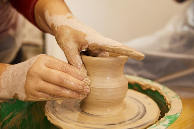 Las manos del hombre están moldeando un jarrón en un lugar de trabajo de cerámica