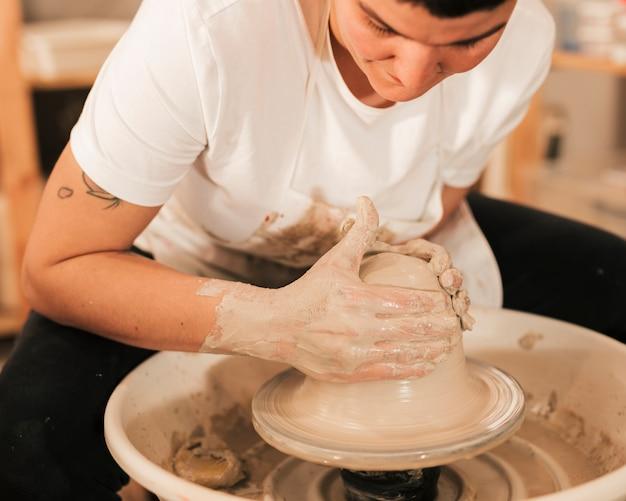 Manos del hombre haciendo olla de cerámica en la rueda de alfarería