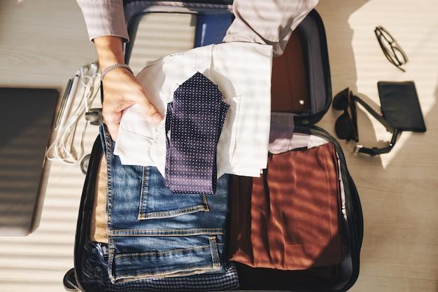 Manos de hombre irreconocible empacando maleta para viajar