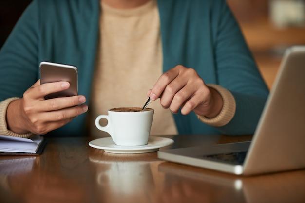 Manos del hombre irreconocible sentado en la cafetería, sosteniendo el teléfono inteligente y revolviendo el café