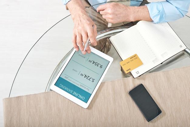 Manos de hombre jubilado con tableta digital y tarjeta bancaria, control de saldo en línea en su cuenta personal mientras está sentado en la mesa