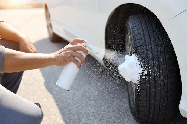 Manos de hombre con limpiador en aerosol en la rueda o neumático de automóvil con efecto de luz solar