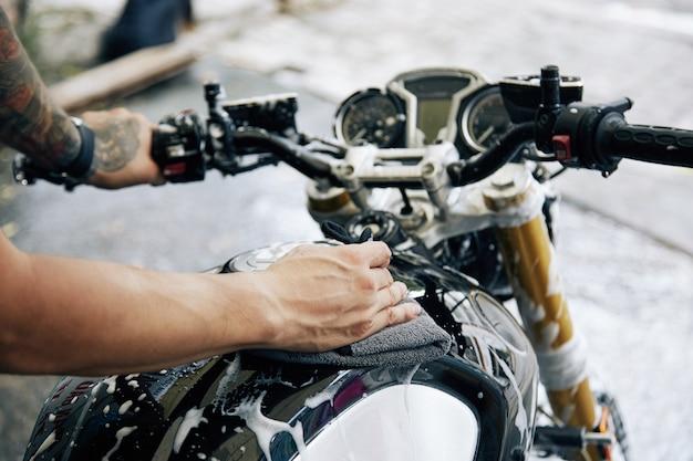 Manos del hombre limpiando la espuma de limpieza de su motocicleta con un paño suave