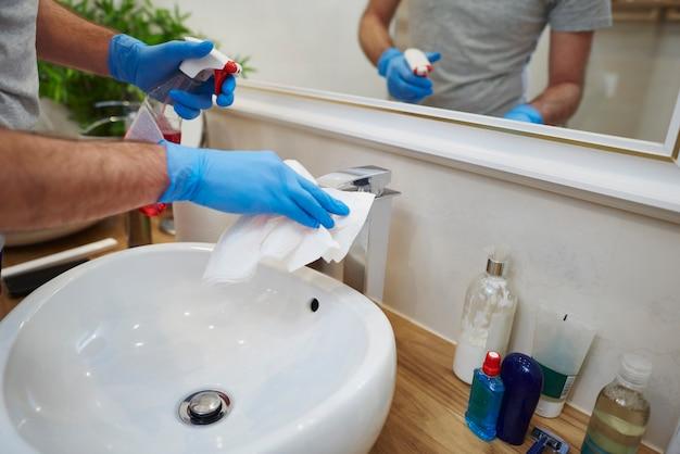 Manos del hombre limpiando el fregadero en el baño.