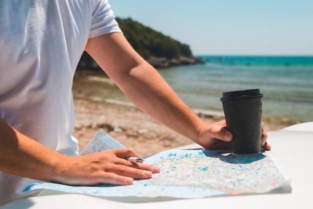 Las manos del hombre en el mapa en el capó del coche sosteniendo la taza de café en verano, vacaciones en el mar