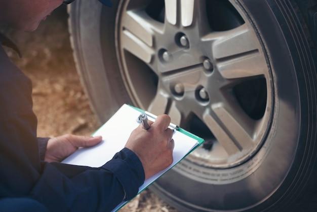 Manos del hombre mecánico que controlan los neumáticos del coche al aire libre en el garaje de automóviles del servicio del sitio para los servicios del centro móvil automotriz. taller técnico de reparación, control de neumáticos, vehículos de motor de automóviles, servicio de manos mecánicas