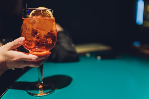 Manos de hombre y mujer animando con copas de champán rosa.