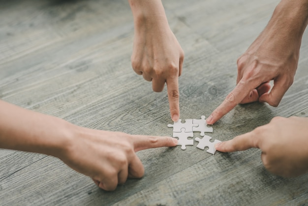 Las manos del hombre y de la mujer que ponen los rompecabezas juntan rompecabezas