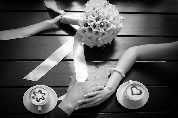 Las manos del hombre y la mujer y las tazas de café sobre la mesa con bouquet de bodas