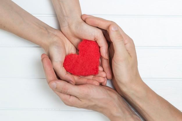 Las manos de un hombre y una mujer tienen un corazón rojo en sus manos. un símbolo de amor.