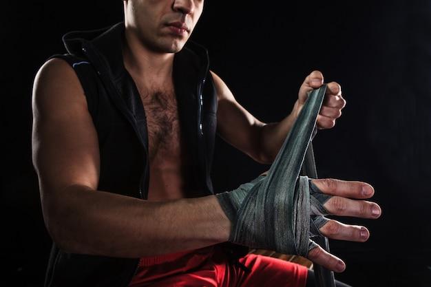 Las manos del hombre musculoso con vendaje