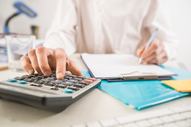 Las manos del hombre de negocios con la calculadora en la oficina y los datos financieros que analizan la cuenta.