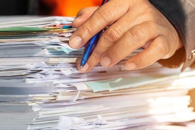 Manos de hombre de negocios comprobación de documentos archivo papeleo mercado financiero
