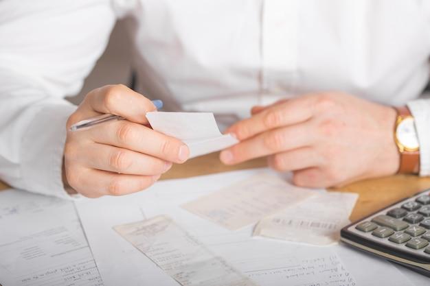 Manos del hombre de negocios que analizan la factura en la computadora portátil mientras que controla cuentas. vista posterior de la factura de cheques mientras los empareja en la computadora. primer de las manos del hombre que calculan gastos financieros.