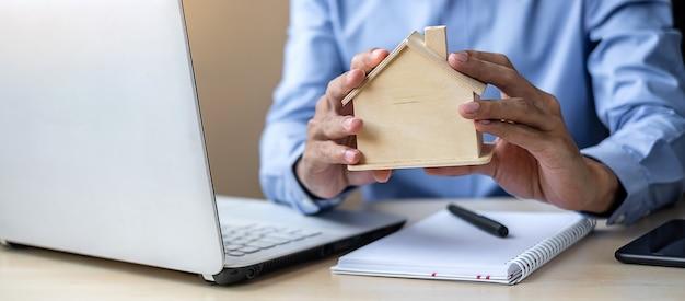 Manos del hombre de negocios que llevan a cabo el modelo de madera de la casa.