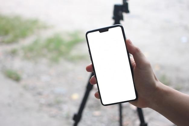 Las manos de un hombre de negocios que sostiene un smartphone en blanco y tienen espacio de la copia.