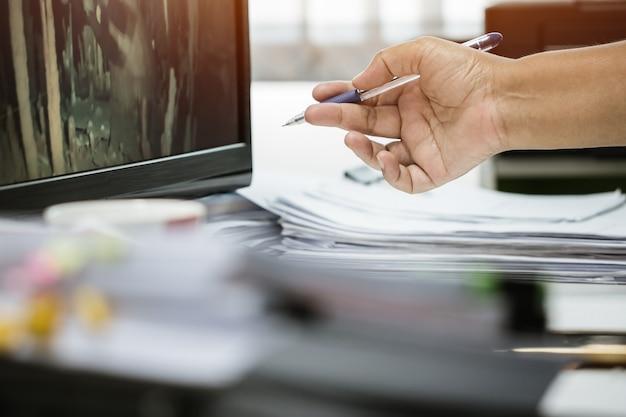 Manos de hombre de negocios que sostienen la pluma trabajando en pilas de archivos de papel en busca de documentos de informes comerciales de información y montones de documentos sin terminar logran en el escritorio de la computadora portátil en la oficina moderna